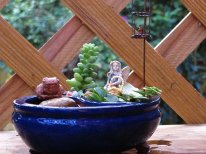 Side view of small blue bonsai with fairy, Timothy and hanging candle - with pond